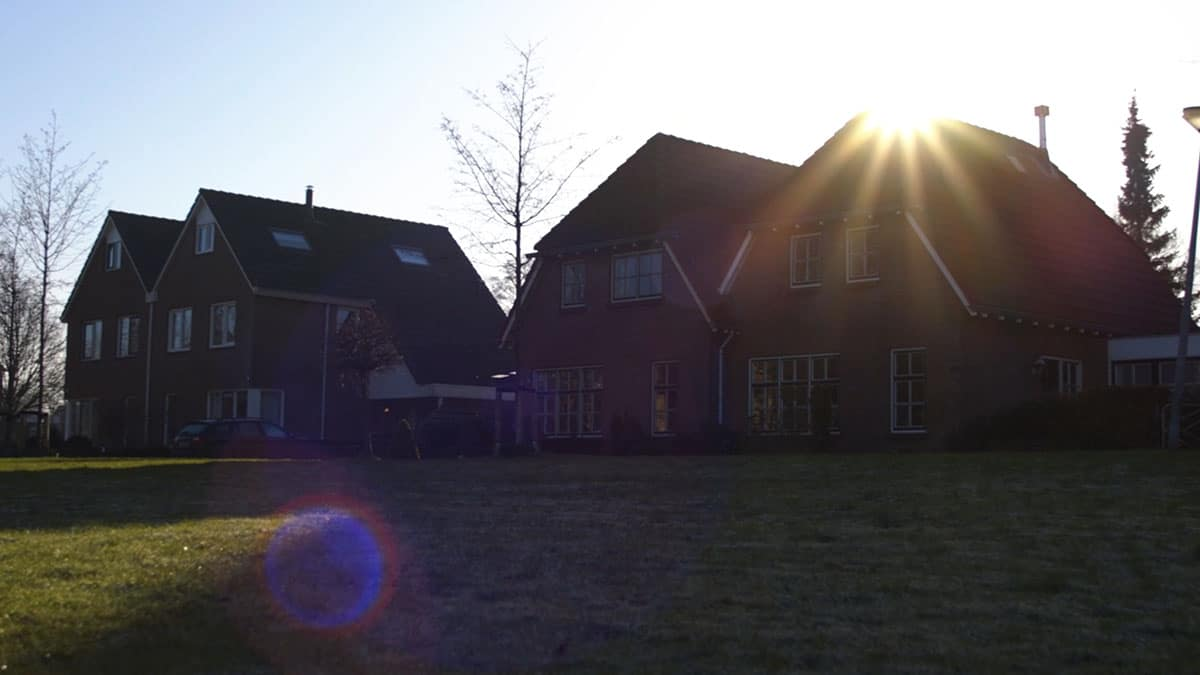 Still van een shot waar de zon achter huizen opkomt