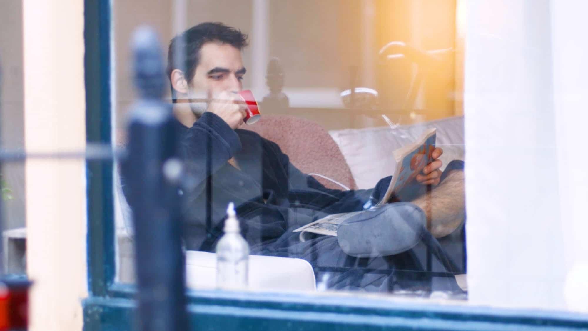 Een man zit koffiedrinkend achter het raam en leest de krant