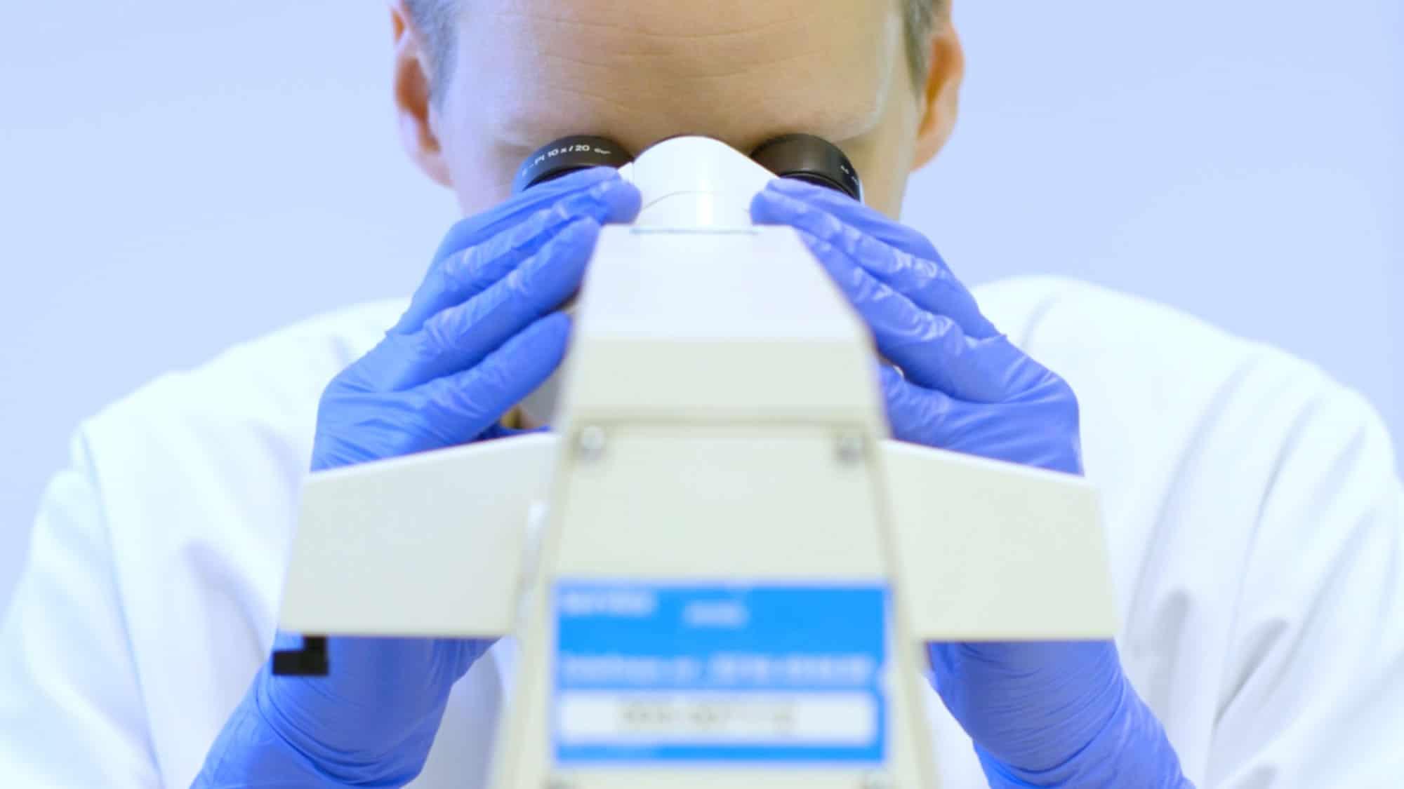 Een laborant analyseert bloed met hulp van een microscoop