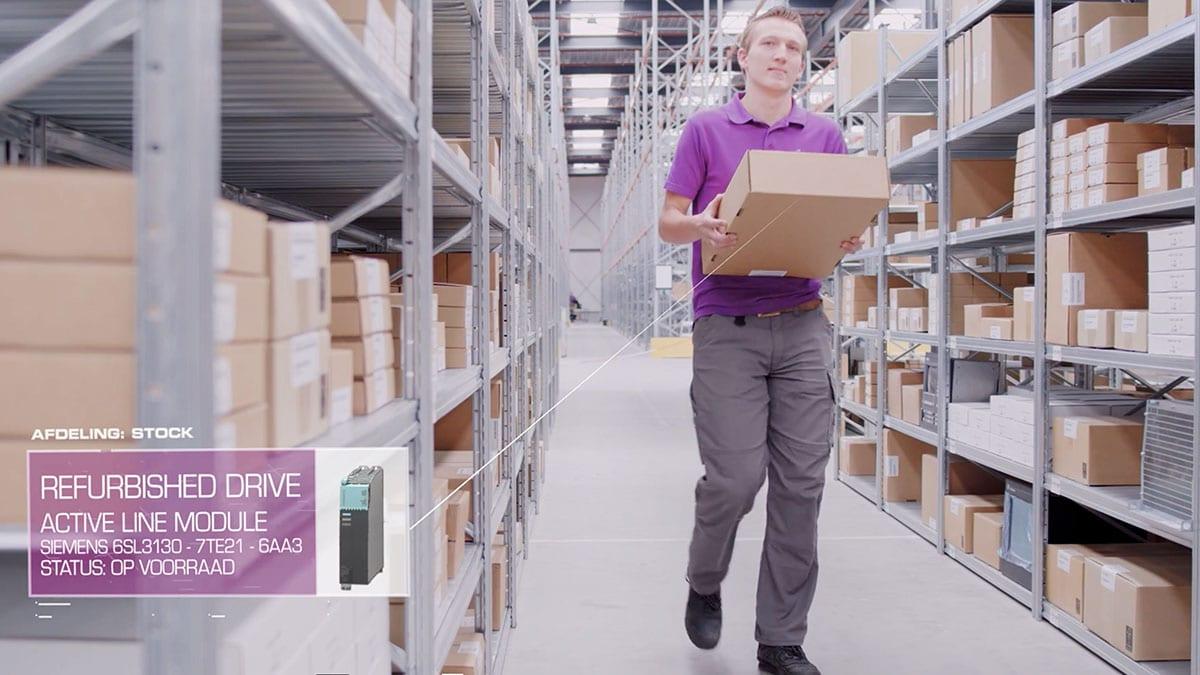 Medewerker van JC electronics brengt een pakket naar het magazijn