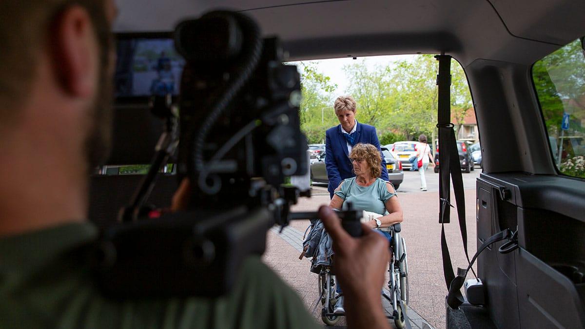 Kevin achterin de auto filmt een vrouw in een rolstoel die de auto in wordt geschoven